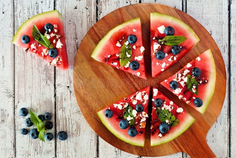 Wassermelonenpizza mit Blaubeeren, Feta und Minze auf Umhüllung verschalen stockfotografie