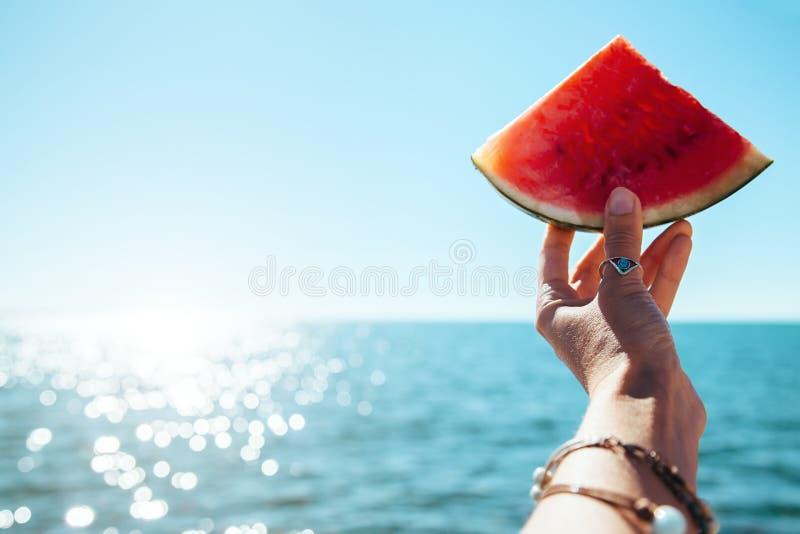 Wassermelonenscheibe in der Frau überreichen Meer lizenzfreie stockfotografie