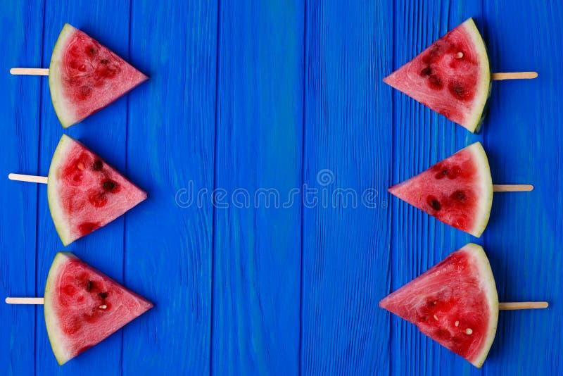 Wassermelonenscheiben auf blauem hölzernem Hintergrund, freier Raum für adve lizenzfreie stockbilder