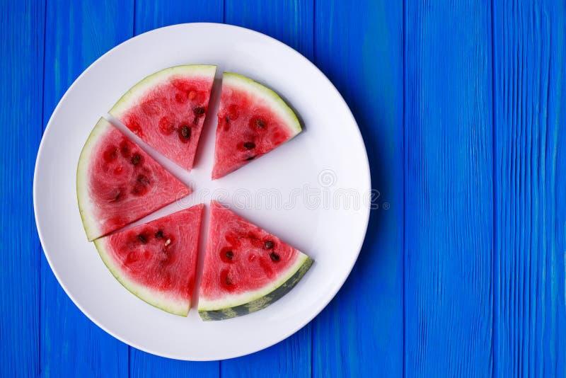Wassermelonenscheiben auf einer weißen Platte auf blauem hölzernem Hintergrund, Franc stockbild
