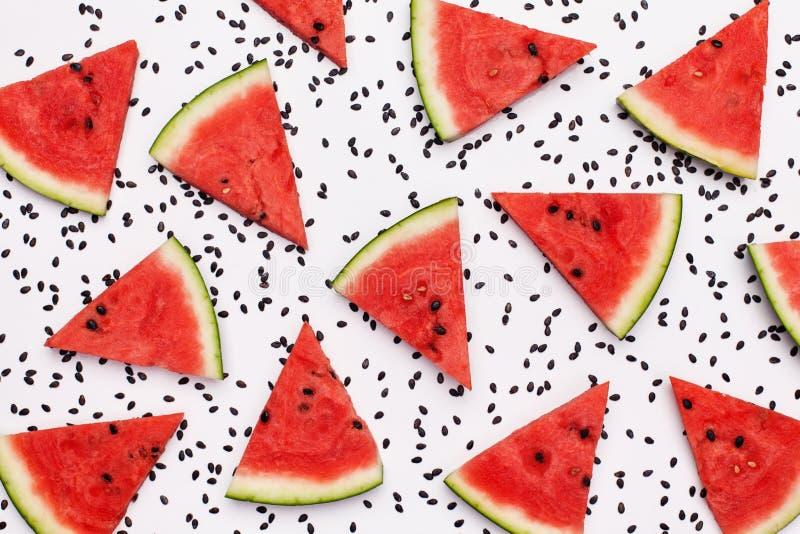 Wassermelonenscheiben unter schwarzen Melonensamen auf weißer Oberfläche lizenzfreies stockbild