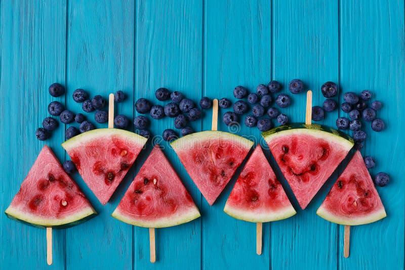 Wassermelonenscheibenpopslices und -blaubeeren auf einer blauen hölzernen Rückseite lizenzfreie stockbilder