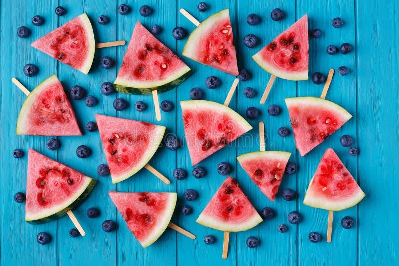 Wassermelonenscheibenpopslices und -blaubeeren auf einer blauen hölzernen Rückseite stockfotografie