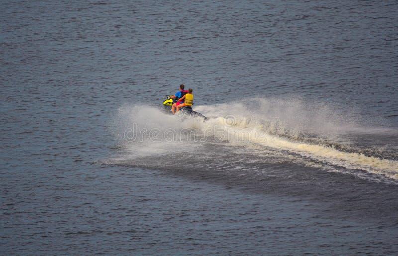 Wassermotorrad fährt schnell auf die Wasseroberfläche stockfotos