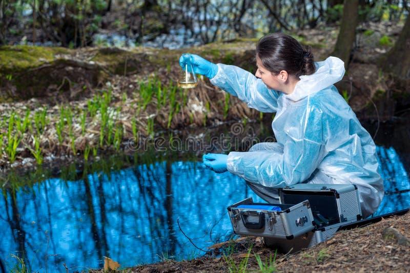 Wasserprobe von einem Waldfluß in einer Flasche in den Händen eines Ökologen lizenzfreie stockfotografie