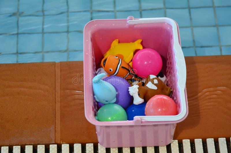 Wasserspielzeugkiste neben Swimmingpool stockfoto