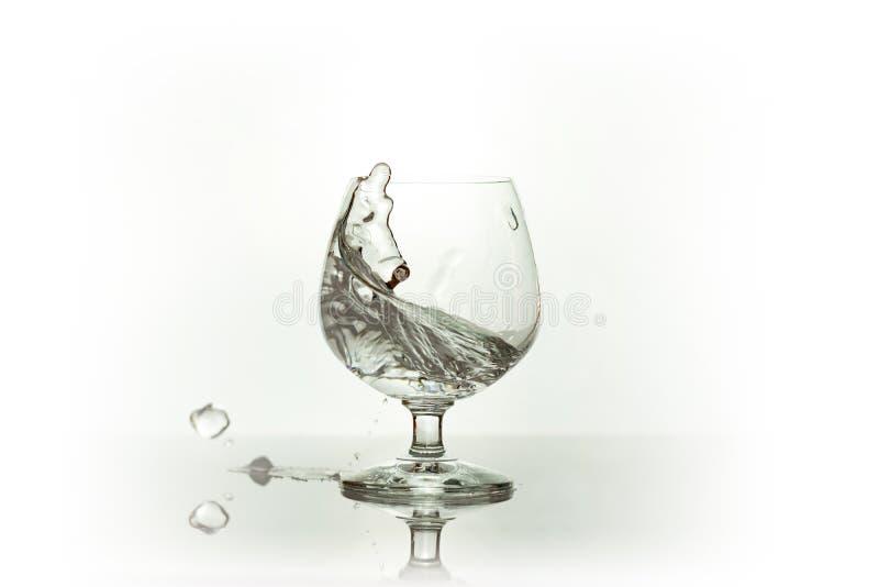 Wasserspray im Weinglas W?ssern Sie Spritzen stockfotografie