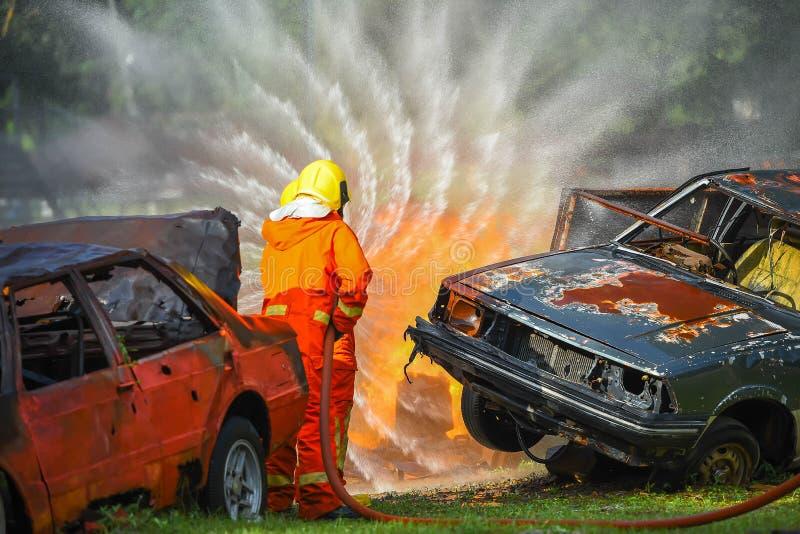 Wasserspray mit zwei Feuerwehrmännern mit dem Hochdruck, zum von Einfassung abzufeuern stockfotografie