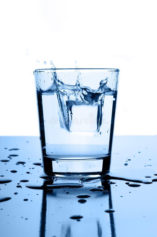 Wasserspritzen im Glas mit Eis lizenzfreies stockbild