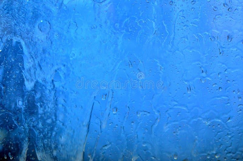 Wasserströme über dem blauen Glas des Fensters, Hintergrund lizenzfreies stockbild