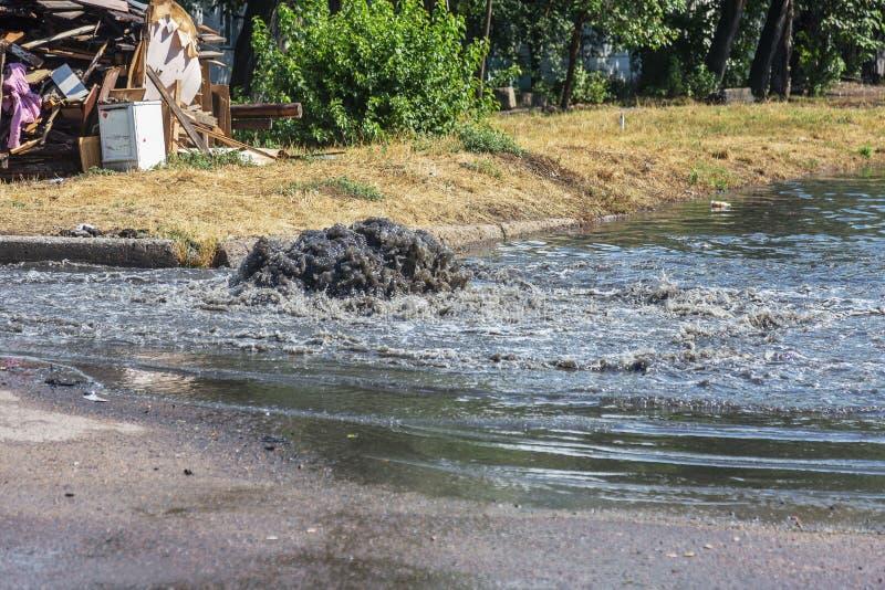 Wasserströme aus Straßenabwasserluke heraus Entwässerungsbrunnen des Abwassers Unfall des Abwassersystems Schmutziger Abwasserwas stockbild