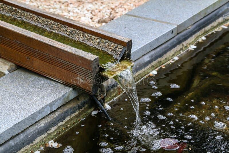 Wasserströme hinunter die Rutsche in den Teich stockfotografie