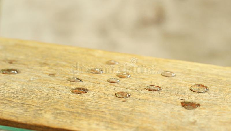 Wassertropfen auf einem Holz stockfotografie