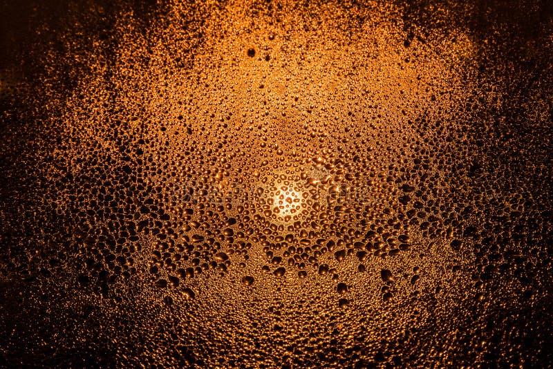 Wassertropfen auf einem nebeligen Fenster angesichts eines Straßenlaterne-Nahaufnahmemakroabstraktionshintergrundes stockfotografie
