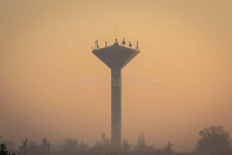 Wasserturm bedeckt im Nebel während des schwermütigen Herbstmorgens lizenzfreie stockbilder