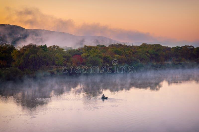 Wasserverdampfung auf dem Fluss an der Dämmerung und am einsamen Fischer auf einem Boot lizenzfreie stockbilder