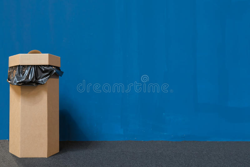 Waste bin or trash bin made of recycled paper, blue painted wall background with copy space, recycle or global warming concept stock photography