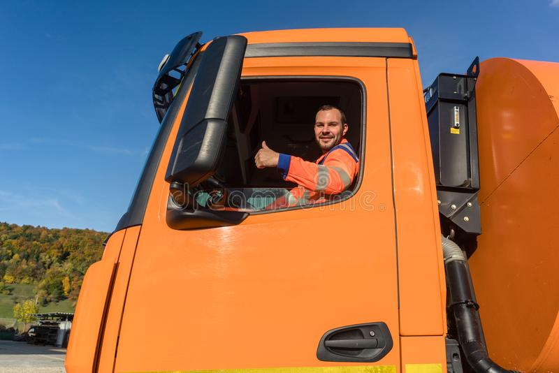 Waste collector driving. RGarbage truck giving thumbs up from the windowr stock image