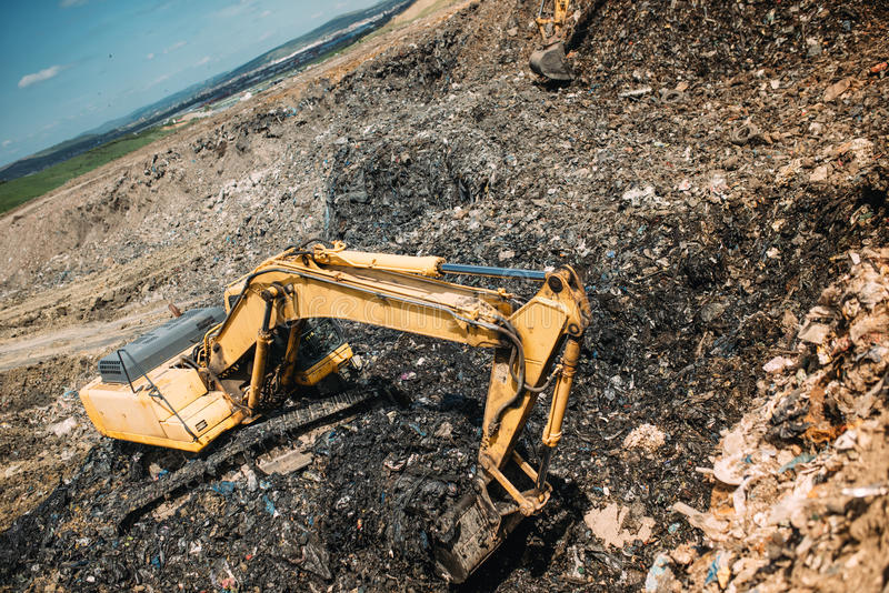 waste on dumping grounds. Details of industrial excavators working, digging and loading stock photos