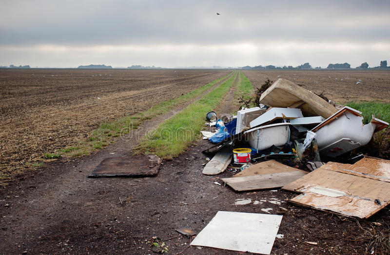 Waste dumping. Household building waste that has been dumped on agricultural land. Environmental polution royalty free stock image