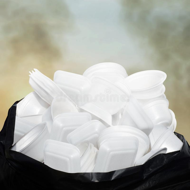 Waste Garbage foam food tray white many pile on the plastic black bag dirty on sky cloud air atmosphere pollution background royalty free stock photography