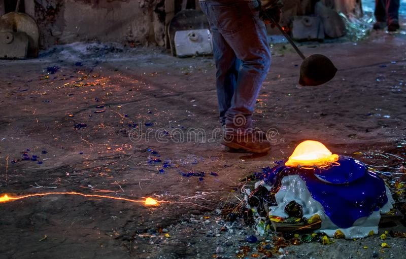 Waste glass glowing red hot at a glass factory. Sept 27 2019 Kokomo Indiana USA; a worker dumps molten glass on a pile of colorful glass waste, as he cleans out stock image