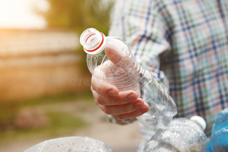 Man`s hand throwing clear transparent recyclable plastic bottle in garbage bin stock images