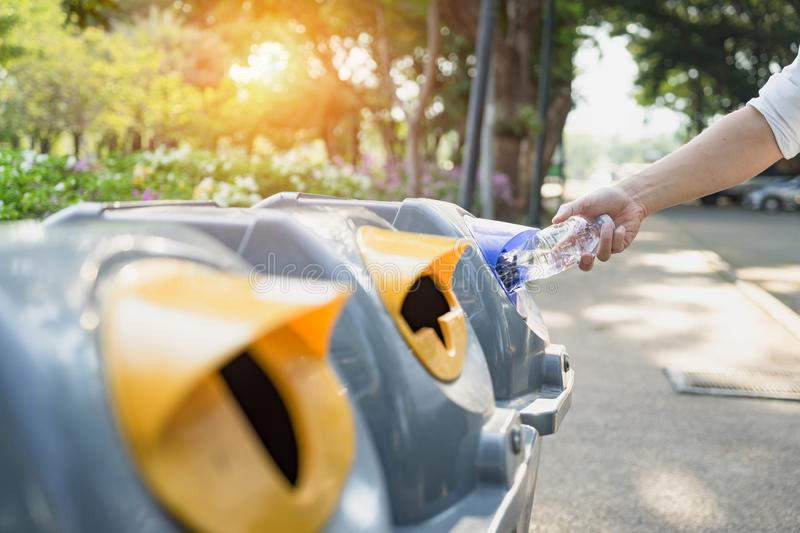 Waste management, Man throwing plastic bottle into recycle bin. Waste separation rubbish before drop to garbage bin to save the. World, environment care stock photo