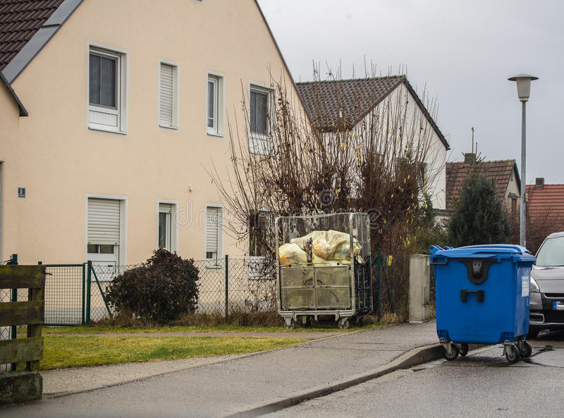 Waste paper in a blue garbage bin and recyclable packaging in yellow bags wait in a driveway for collection. And processing in recycling plants royalty free stock photo