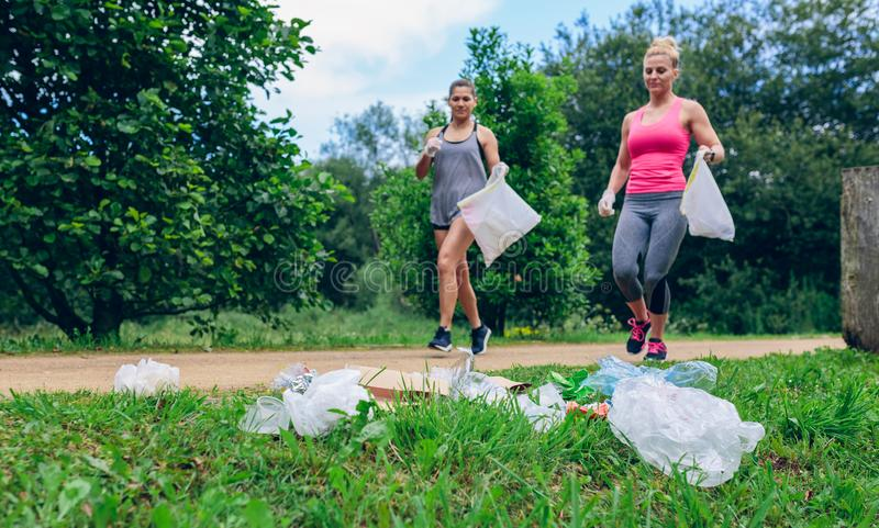 Waste pile and two girls doing plogging royalty free stock photo