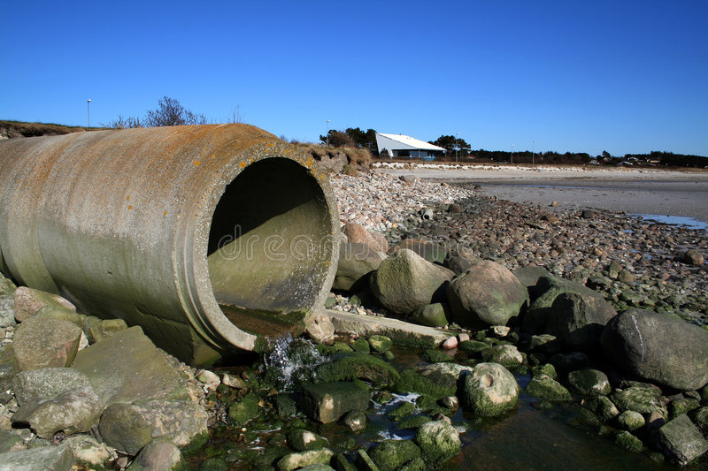 Waste pipe sewage. Sewage waste pipe or drain polluting beach. concrete pipeline with water running out stock photography