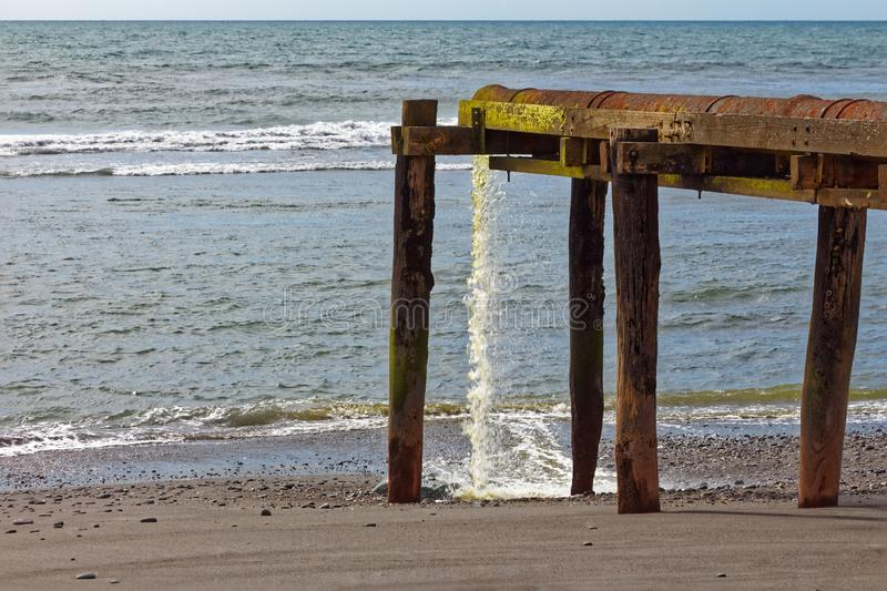 Waste pipe spewing into the sea. On New Zealand`s west coast royalty free stock image