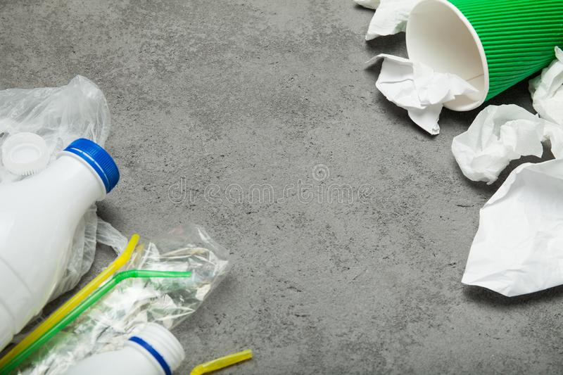 Waste with a plastic bottle, plastic and paper on a gray background, top view. Empty space for text royalty free stock image