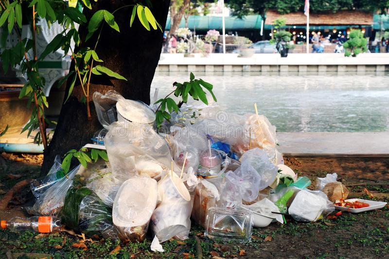 Waste plastic heap, Garbage plastic, Waste dump, Pile plastic bags and wet food waste at the the tree and river background stock photos