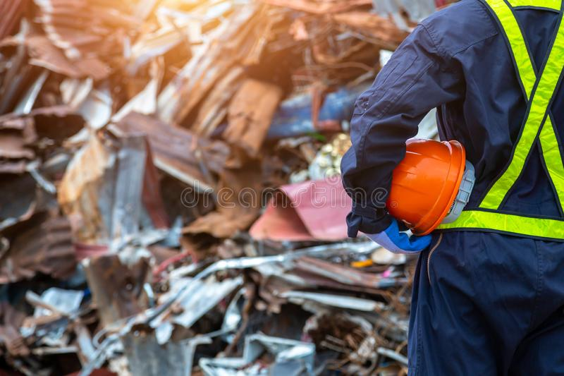 Waste recycling engineer holding a Safety helmet suit standing in the outdoor recycling center have a metal scrap pile in the. Background. workers in landfill royalty free stock images