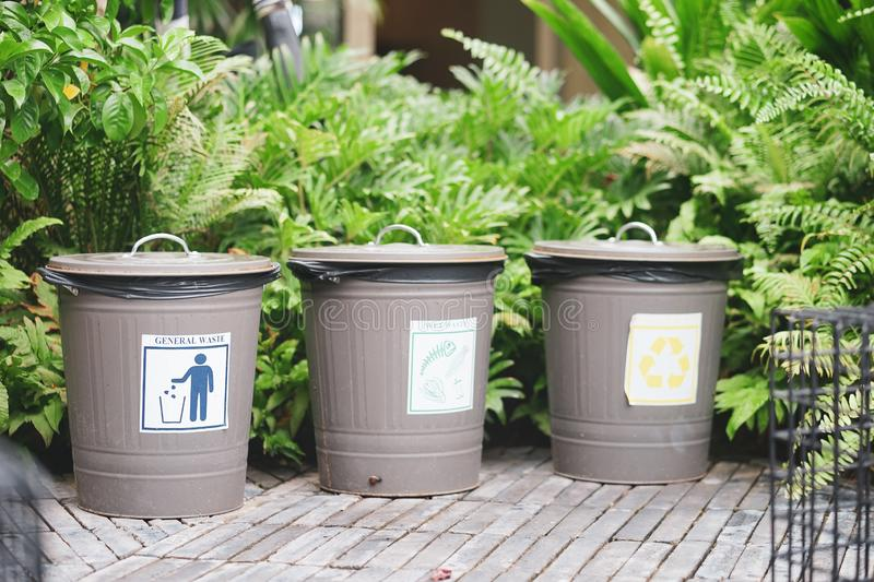 Waste separation. 3 classic trash cans in the public garden with label general waste, wet waste and recycle sign stock photo