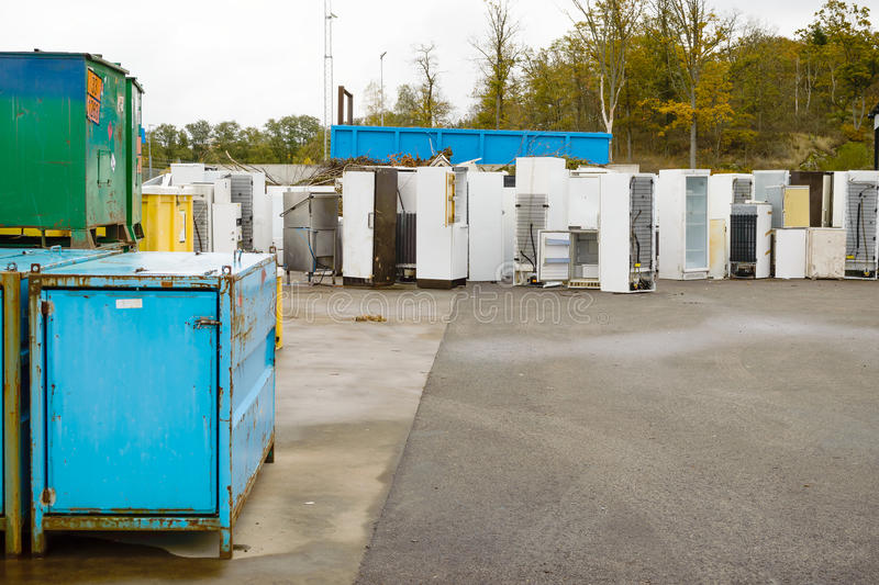 Waste separation. Old used refrigerators and freezers are stored separately in the waste station. Here are some standing together with steel crates in foreground royalty free stock photography
