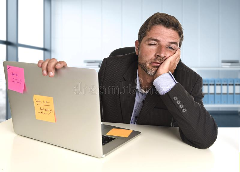 Wasted businessman working in stress at office laptop computer looking exhausted. Young tired and wasted businessman working in stress at office laptop computer stock images