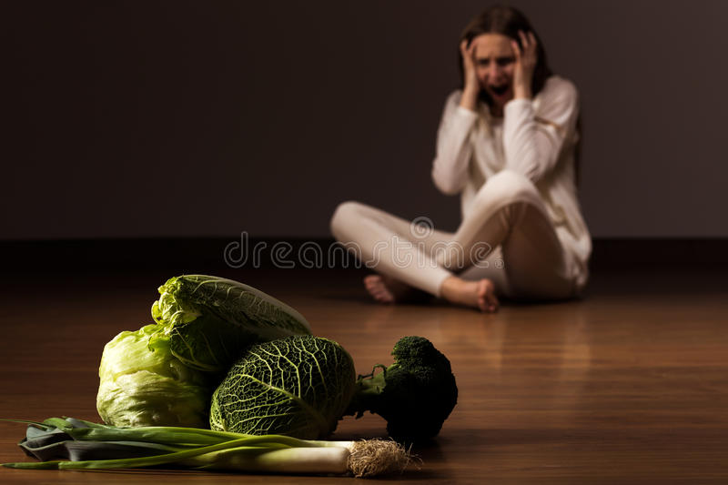 Wasting influence of anorexia. Woman with eating disorder looking at the vegetables and shouting royalty free stock images