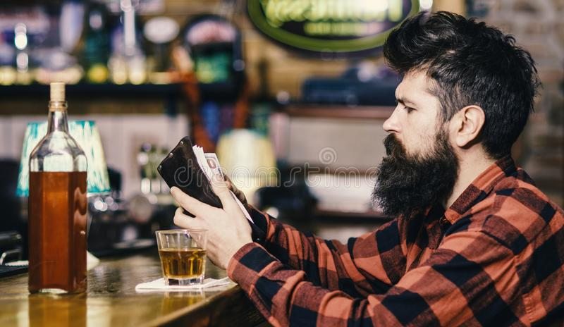 Wasting money on alcohol concept. Guy spend leisure in bar,. Defocused background. Depressed and sad man sit alone in bar or pub near bar counter. Hipster holds stock photo