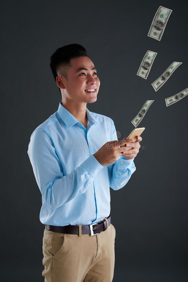 Wasting money. Cheerful young man looking at money flow coming out of his smartphone royalty free stock image
