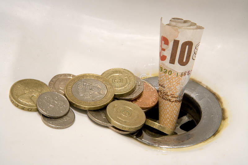 Wasting money concept. British ten pound note and coins going down plughole or drain, wasting money concept stock photos