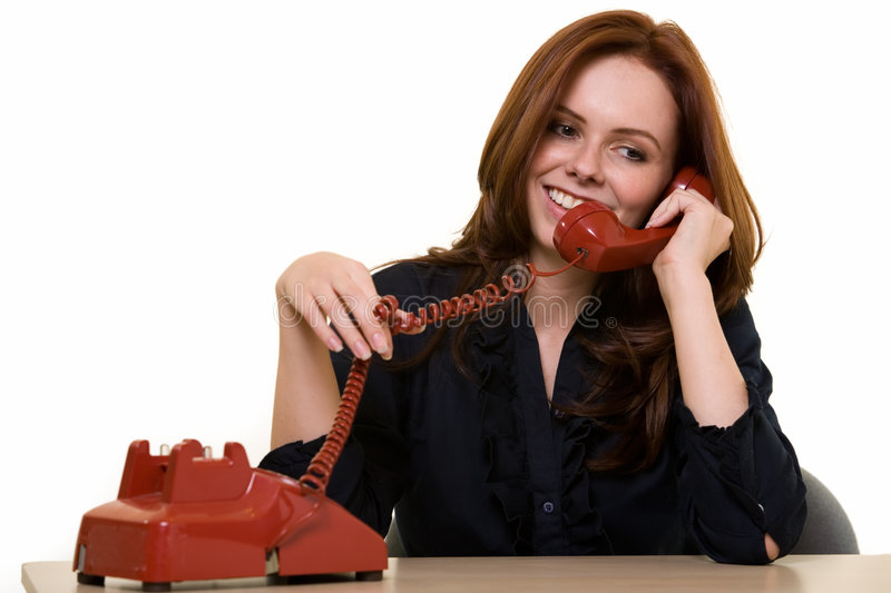 Wasting office time. Attractive young brunette woman in business suit talking on an old style red phone smiling while sitting at a desk over white as if making stock photography