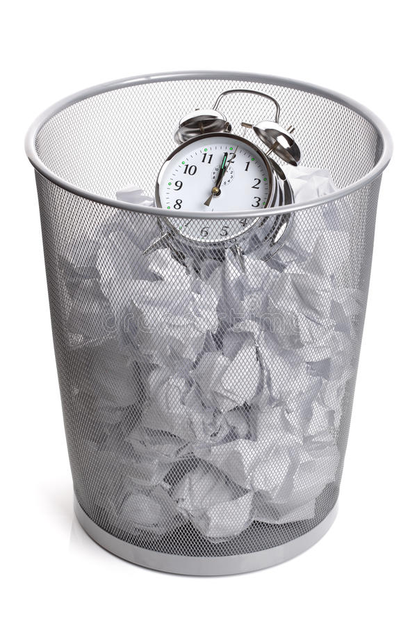 Wasting time. Alarm clock in a wastepaper bin concept for a time waste of time stock photography