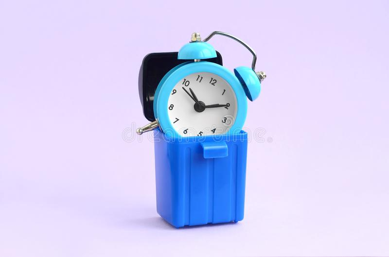 Wasting time concept. Alarm clock in trash bin royalty free stock image