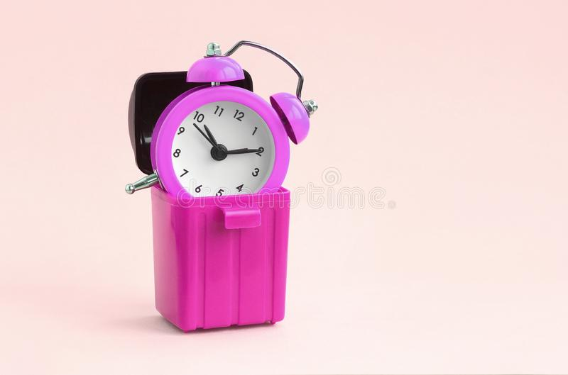 Wasting time concept. Alarm clock in trash bin. Wasting time concept. Pink alarm clocks in plastic trash bin on peach background. Bad and wrong time management stock image