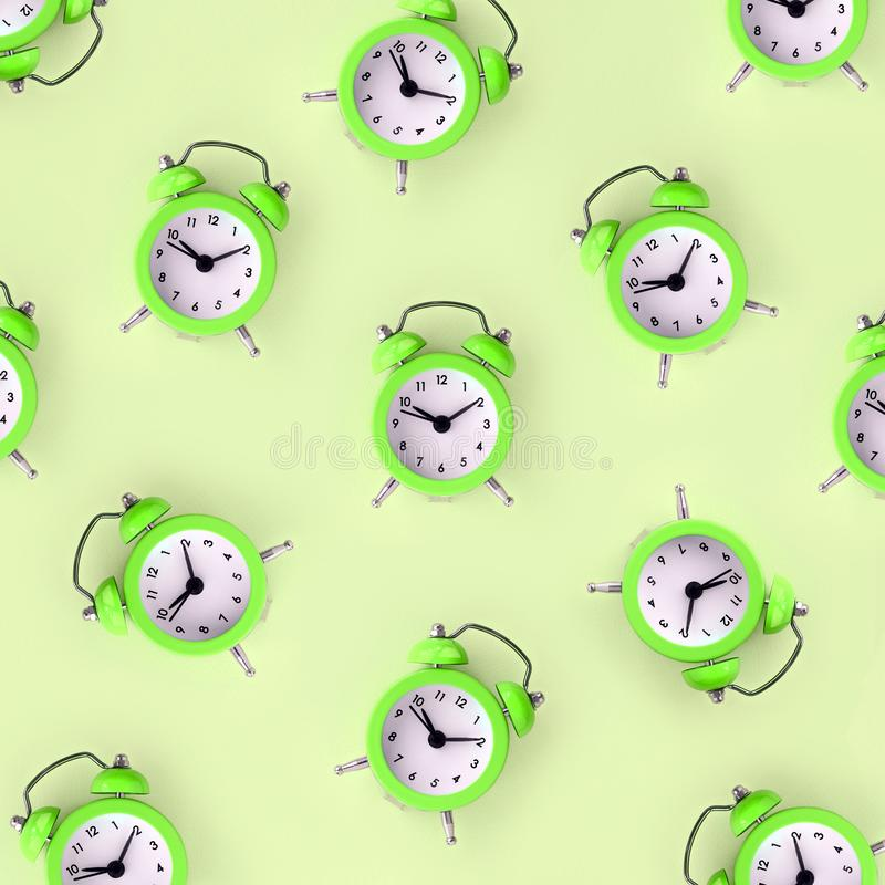 Wasting time concept. Many green alarm clock. Flat lay retro beautiful new alarm clock on lime color background. Minimal pattern. Top view. Wasting time concept stock image