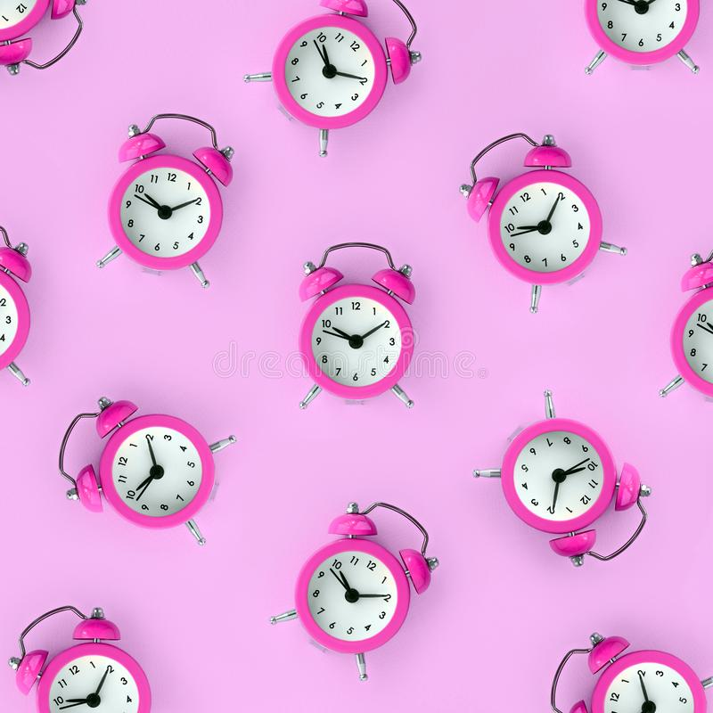 Wasting time concept. Many purple alarm clock. Flat lay retro beautiful new alarm clock on purple color background. Minimal pattern. Top view. Wasting time royalty free stock image