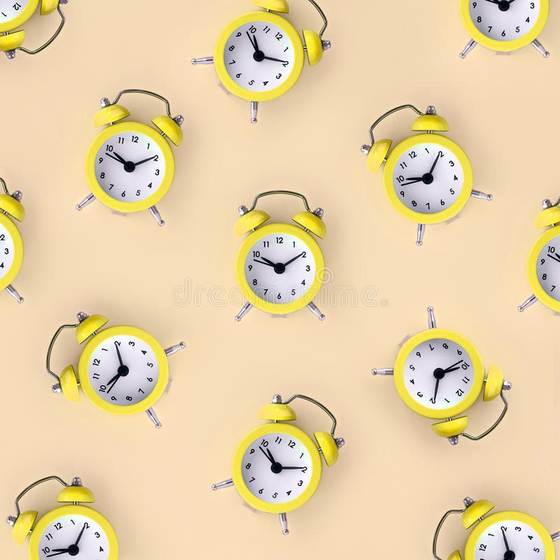 Wasting time concept. Many yellow alarm clock. Flat lay retro beautiful new alarm clock on yellow cream color background. Minimal pattern. Top view. Wasting time stock images