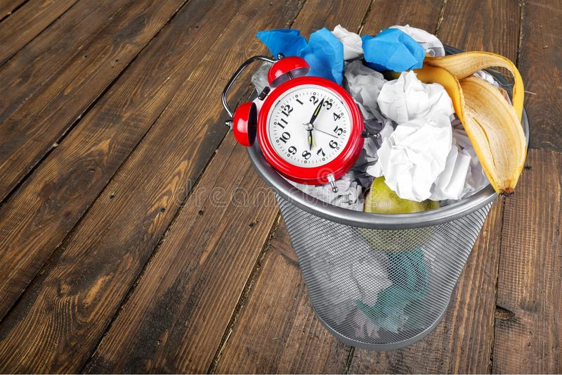 Wasting Time. Time Garbage Wastepaper Basket Clock Business Alarm Clock royalty free stock images